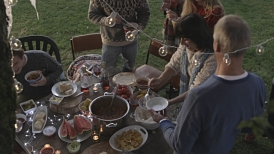 Overhead view of family and friends at a garden party having food and drinks.