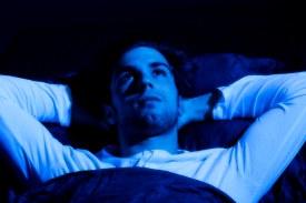 Young man lying awake