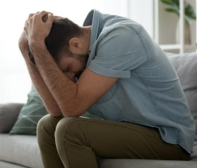 Depressed sad man sitting on couch holding head in hands