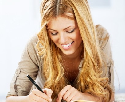 Portrait of a cheerful blonde woman writing diary.